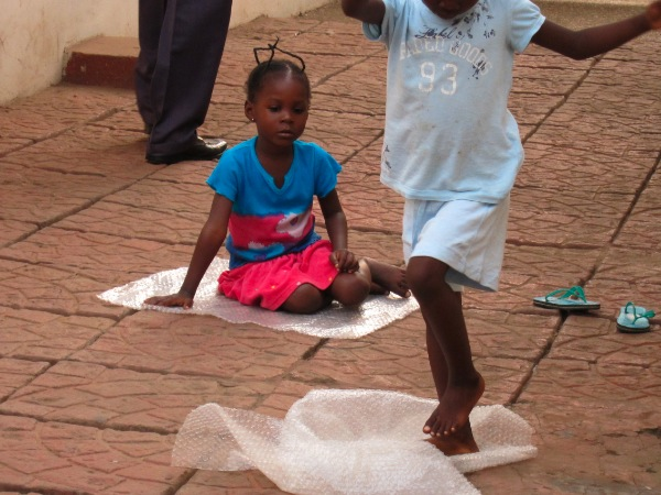 Ghanaian kids play with bubble wrap